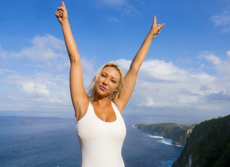 Sonrisa rubia feliz y hermosa joven de la mujer alegre en el paisaje tropical del acantilado de la playa que disfruta de la parti imagenes de archivo