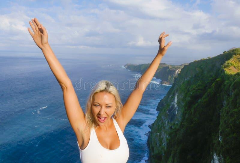 Sonrisa rubia feliz y hermosa joven de la mujer alegre en el paisaje tropical del acantilado de la playa que disfruta de la parti imágenes de archivo libres de regalías