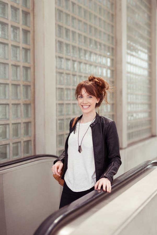 Sonrisa señora bastante joven Taking la escalera móvil foto de archivo libre de regalías