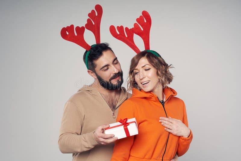 Sonrisa sonriente feliz de los trajes de los ciervos de la Navidad de los pares que lleva imagen de archivo libre de regalías