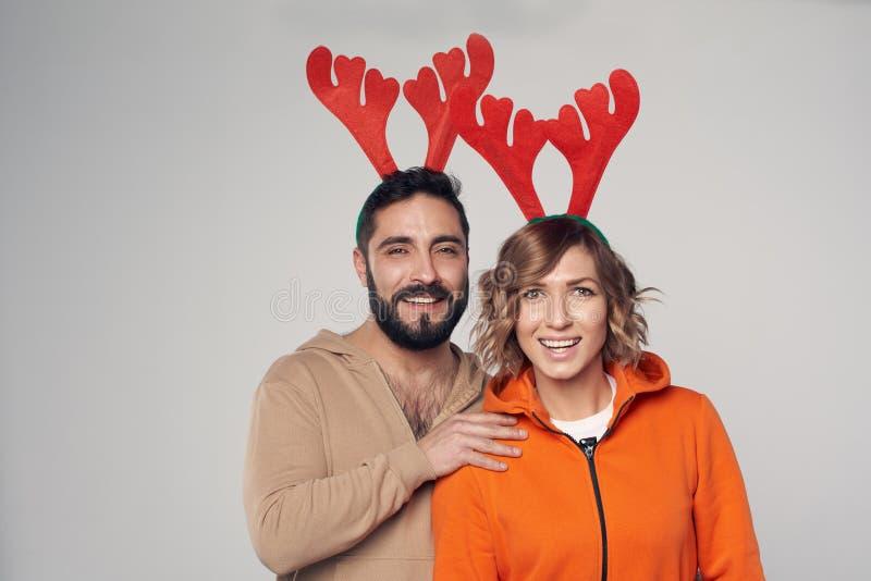 Sonrisa sonriente feliz de los trajes de los ciervos de la Navidad de los pares que lleva fotos de archivo