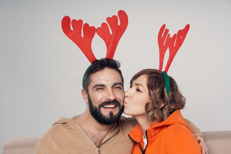 Sonrisa sonriente feliz de los trajes de los ciervos de la Navidad de los pares que lleva fotografía de archivo