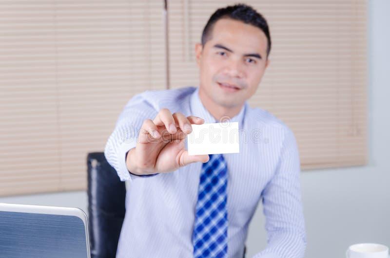 Sonrisa tailandesa asiática del hombre de negocios y mostrar el negocio blanco en blanco c foto de archivo