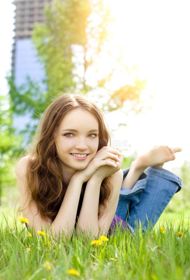Sonrisa triguena de la muchacha del adolescente en prado imagen de archivo