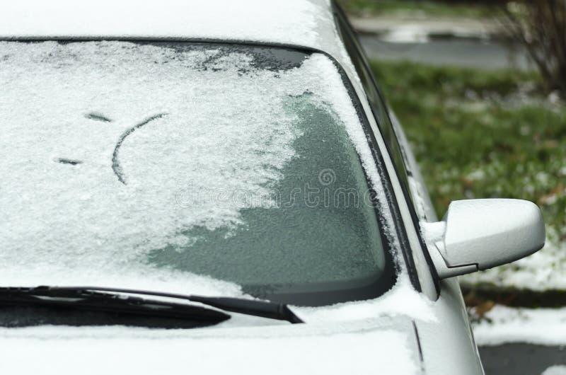 Sonrisa triste en la ventanilla del coche en invierno Primera nieve foto de archivo libre de regalías
