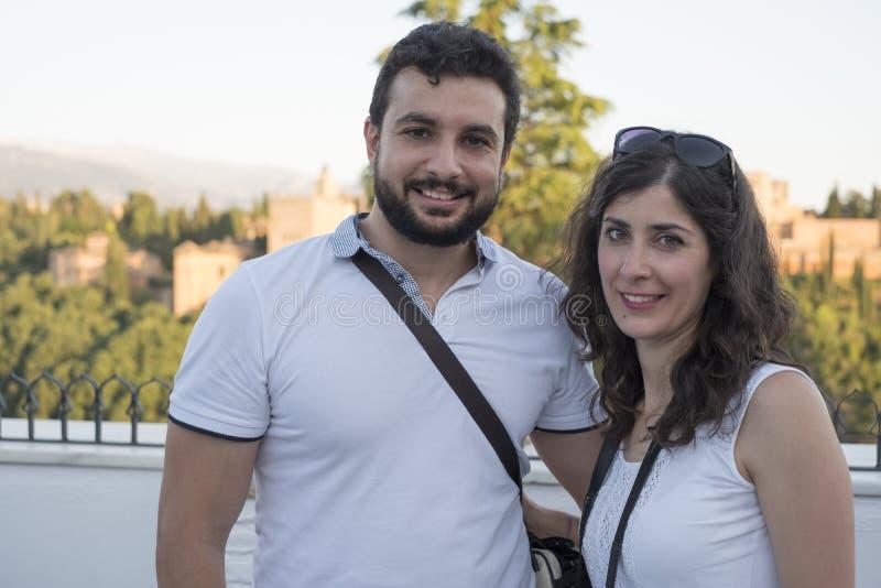 Sonrisa turística de los pares que presenta en Granada fotografía de archivo libre de regalías