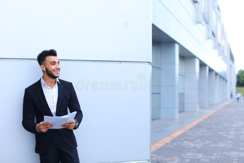 Sonrisa y miradas árabes jovenes hermosas del hombre de negocios del individuo lejos con imagenes de archivo