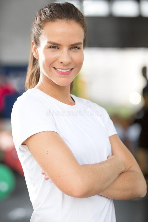 Sonrisa y mujer confiada en el gimnasio de la aptitud imagen de archivo