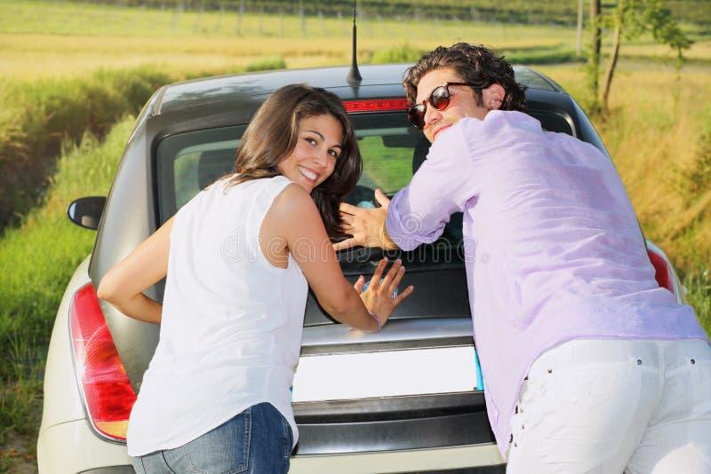 Sonrisa y pares divertidos que empujan un coche fotografía de archivo libre de regalías