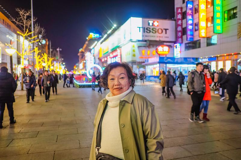 Sonrisa y situación asiáticas del viajero de las mujeres de la foto del retrato en wangfujing la calle que camina famosa en Pekín fotografía de archivo libre de regalías