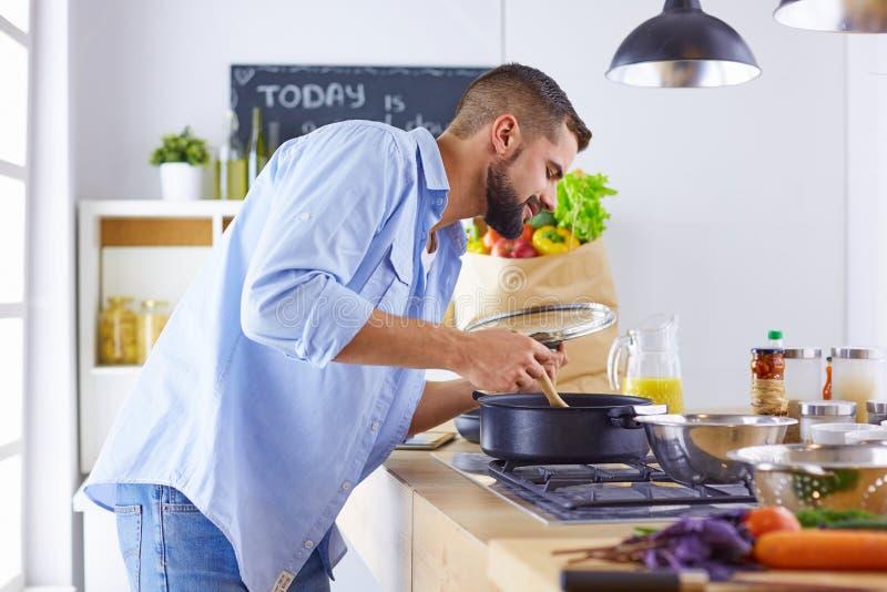 Sonrisa y situación confiada del cocinero en una cocina grande que prueba un plato cocinado fotografía de archivo