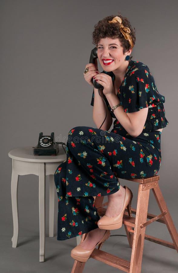 Sonrisas bobas modelas de la muchacha mientras que en el teléfono pasado de moda fotografía de archivo