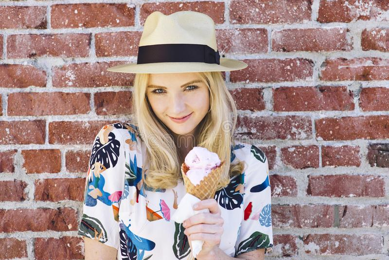 Sonrisas caucásicas de la mujer como ella lleva a cabo una diversión del sombrero del verano del cono de helado foto de archivo