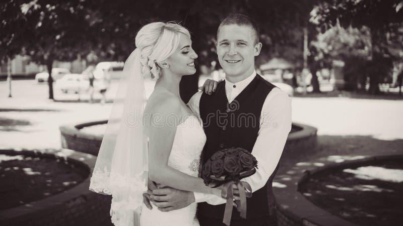 Sonrisas jovenes alegres de la novia cuando ella se coloca con su marido Pares casados Marido y esposa Primer Rebecca 36 fotos de archivo