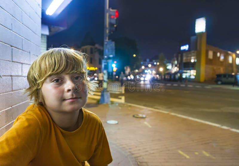 Sonrisas lindas del muchacho cansadas mientras que se sienta afuera por noche foto de archivo