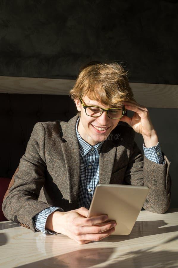 Sonrisas masculinas hermosas alegres que leen la PC de la tableta en el café fotos de archivo