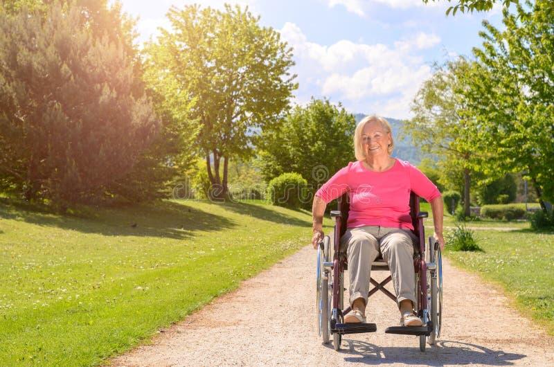 Sonrisas mayores de la mujer mientras que está asentado en silla de rueda foto de archivo