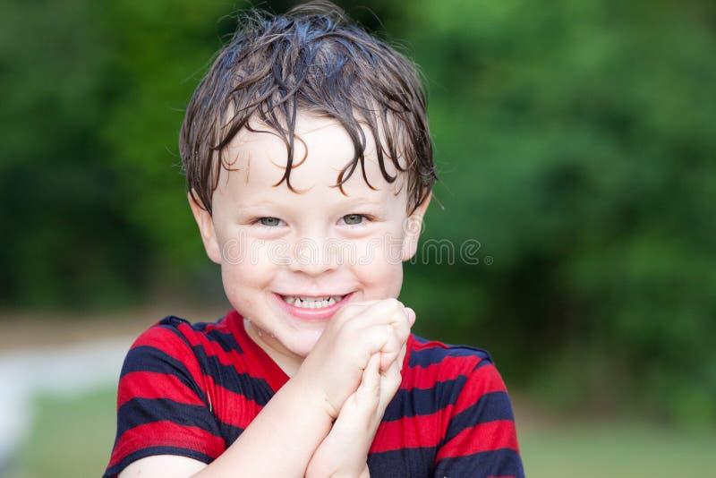 Sonrisas mojadas de un muchacho que juegan afuera imágenes de archivo libres de regalías