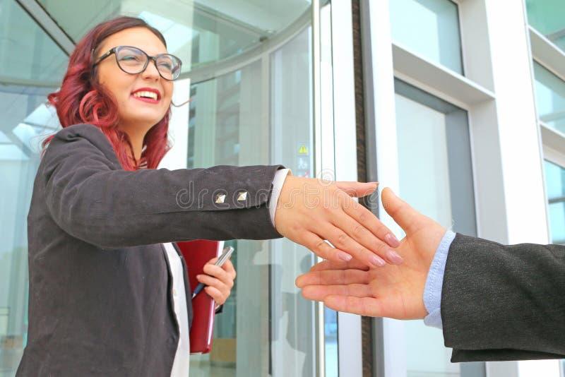 Sonrisas y apretones de manos femeninos del ejecutivo de la reunión de negocios imagenes de archivo