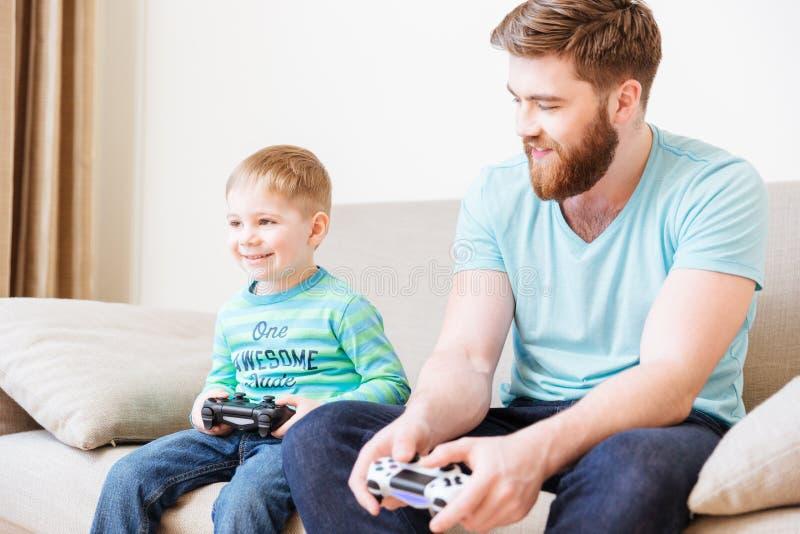 Sonsammanträde på soffan och speladataspelar med fadern arkivfoton
