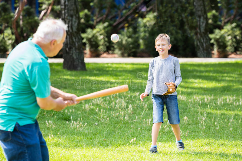 Sonson och farfar som spelar baseball arkivbilder