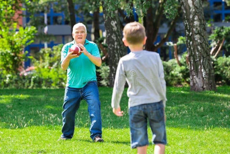 Sonson och farfar som spelar rugby arkivfoton