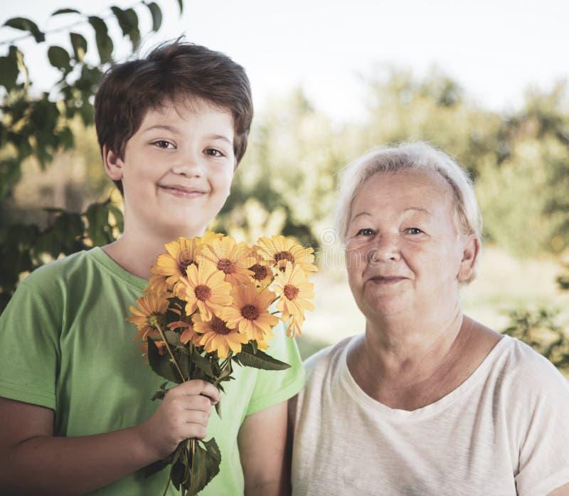Sonsonen ger farmorblommor, ett barn med en gåva för en äldre kvinna i en sommarträdgård royaltyfri bild