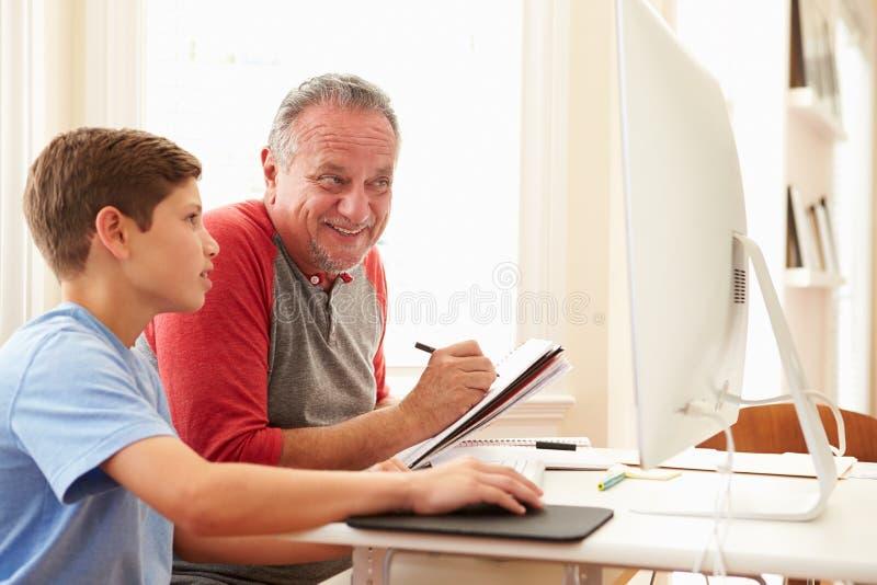 Sonsonundervisningfarfar som använder datoren royaltyfri bild