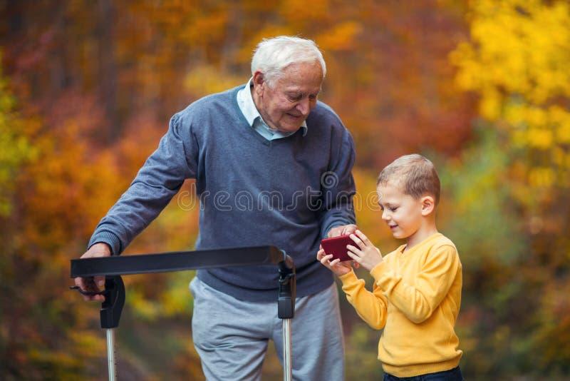 Sonsonvisning något på telefonen i den rörelsehindrade höga farfadern för parkera arkivbilder