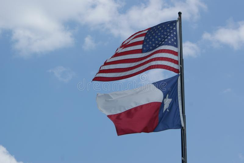 The American and The Texas Flag Blowing In The Wind. royalty free stock images