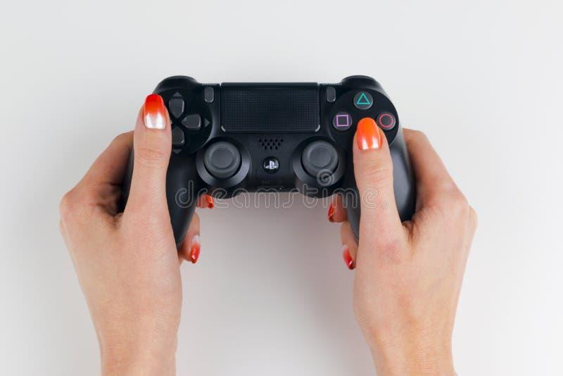 Sony PlayStation 4 het controlemechanisme van het dualshockspel in gamers overhandigt op wit achtergrondstudioschot stock fotografie