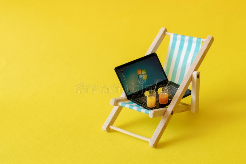 Sony`s miniature laptop on a miniature blue deck chair. Freelance Part time Outsources Job Employment Concept. Work on travel. stock photo