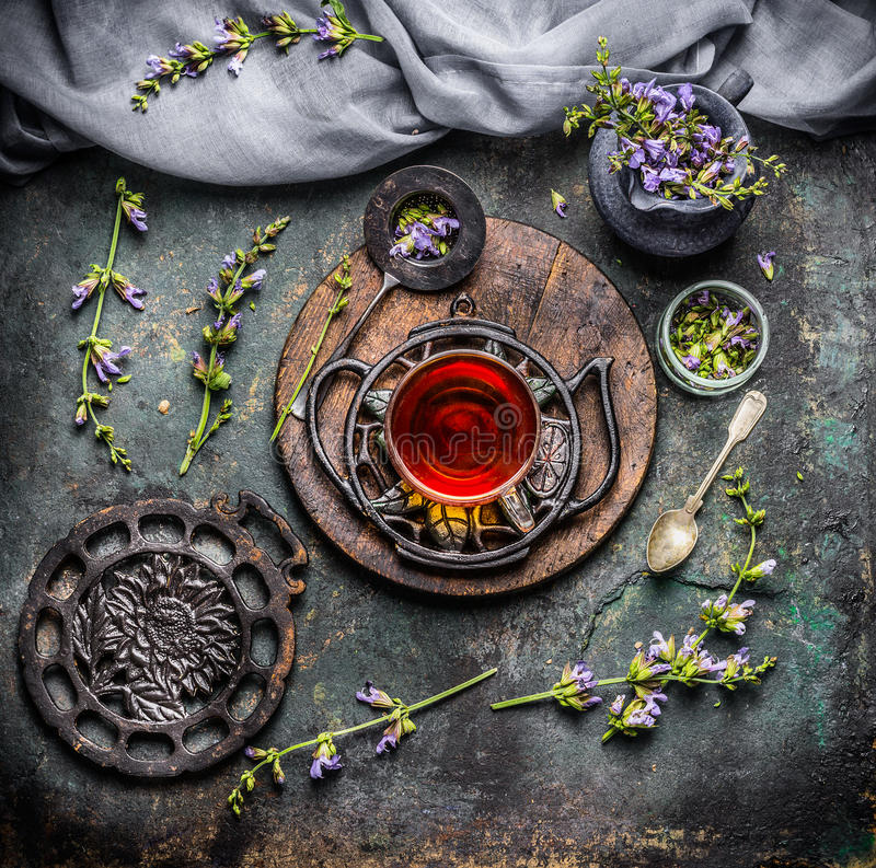 Soothing cup of herbal tea with freshest organic ingredients: herbs and flowers on rustic vintage background with tea tools. Top view stock photography