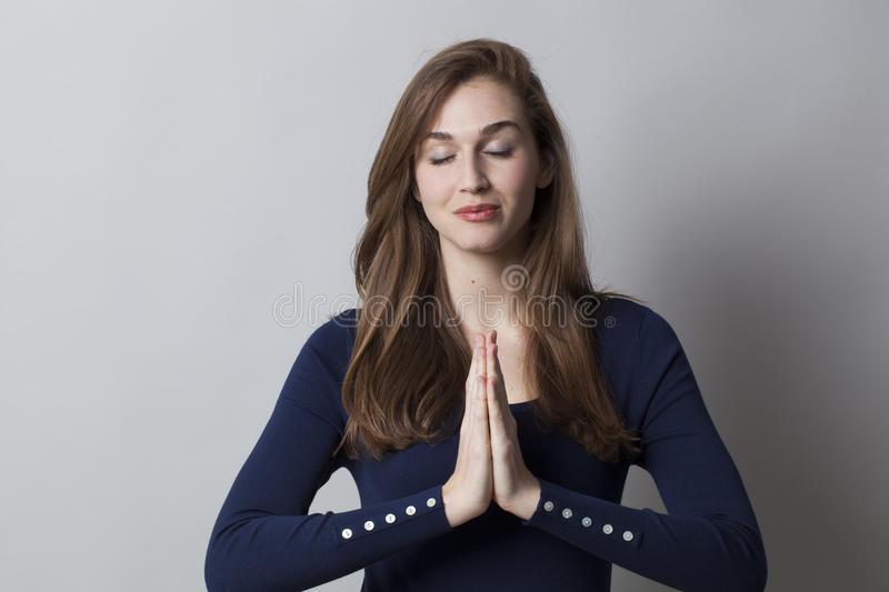 Soothing hands for meditating at work. Meditation concept - zen smiling young woman wearing a smart navy blue sweater holding hands together,closing eyes for stock image