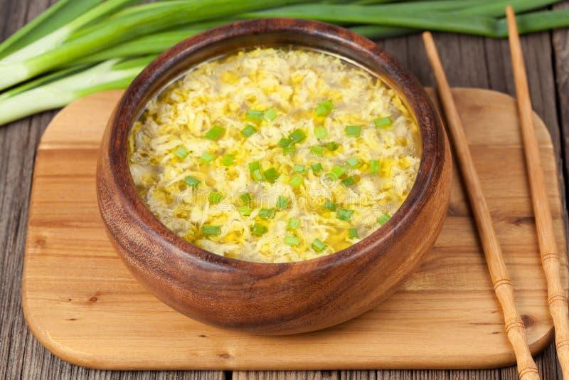 A sopa amarela da gota do ovo com chiken o chinês do caldo imagem de stock