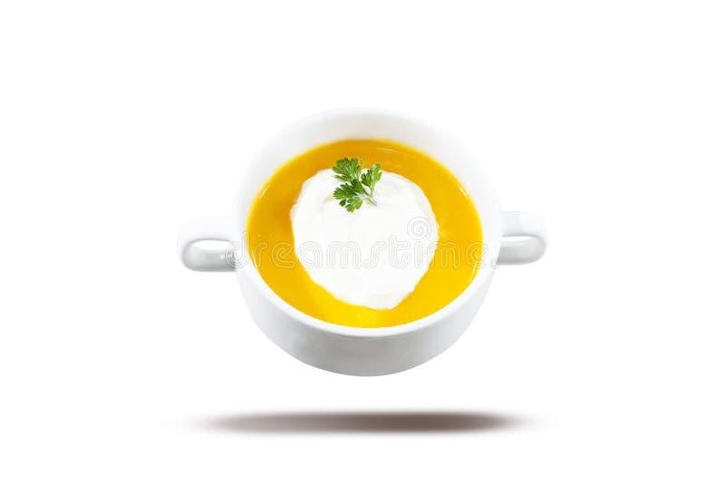 Sopa amarela na bacia branca Sopa da abóbora e da cenoura, servida com creme e salsa Isolado no fundo branco imagem de stock royalty free