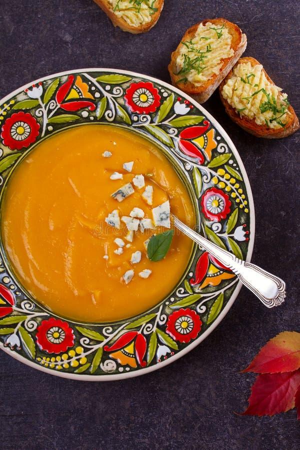 Sopa asada de la calabaza moscada con las tostadas del queso verde y de la mantequilla de ajo Sopa cremosa de la fruta y verdura imagenes de archivo