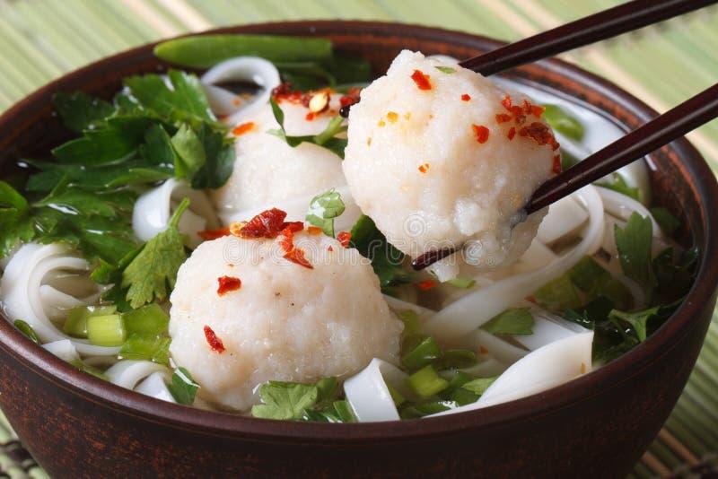 Sopa asiática tradicional con las bolas de pescados y los palillos imagenes de archivo