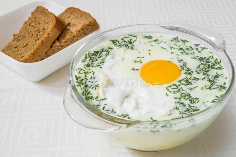Sopa branca do café da manhã saboroso com ovo, em uma placa transparente, pão no fundo Quadro horizontal imagem de stock royalty free