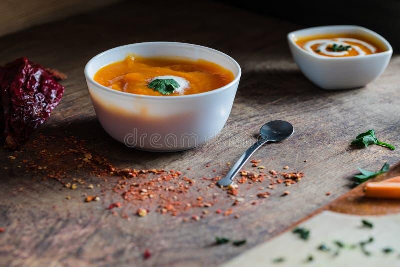 Sopa caseiro da abóbora com creme e salsa em um fundo de madeira imagem de stock