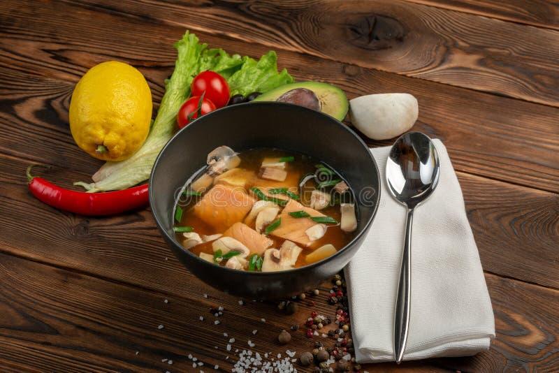 Sopa china con los pescados rojos en una placa negra en un fondo de madera imagen de archivo