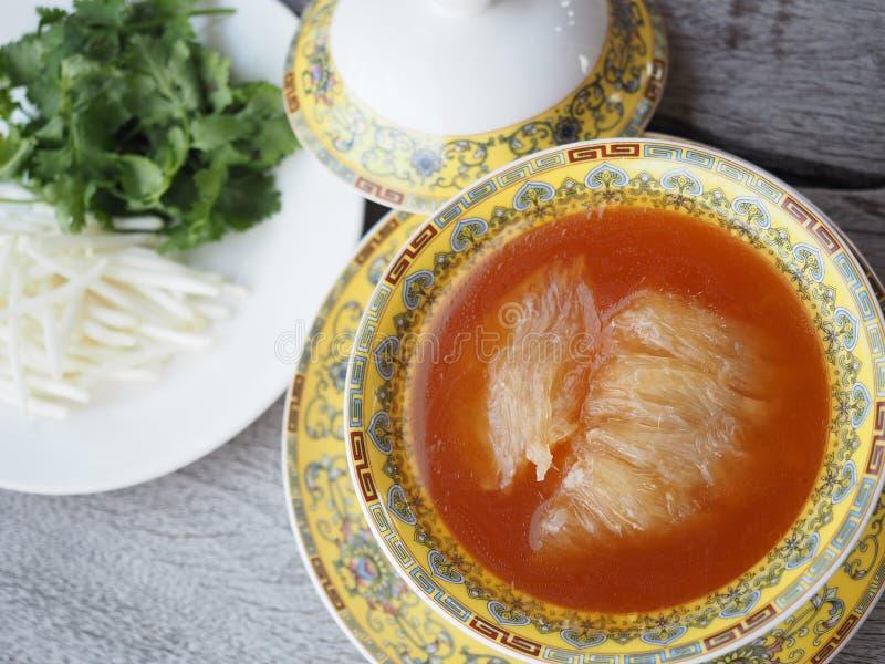 Sopa china de la aleta del ` s del tiburón con servicio de la salsa marrón en cuenco amarillo real imagen de archivo