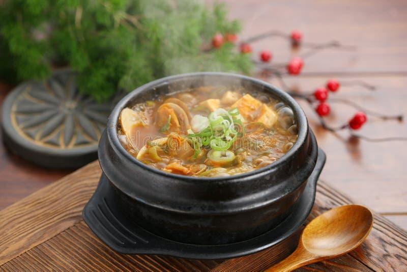 Sopa china de las almejas en cuenco negro en la tabla en restaurante fotografía de archivo