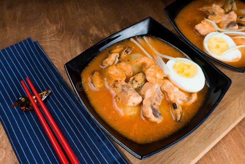 Sopa com camarões na bacia com tomates e ervas na tabela de madeira imagem de stock
