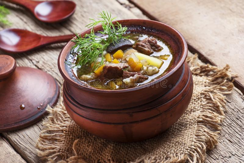 Sopa com cogumelos, carne e cevada, potenciômetros de argila, vintage de madeira foto de stock