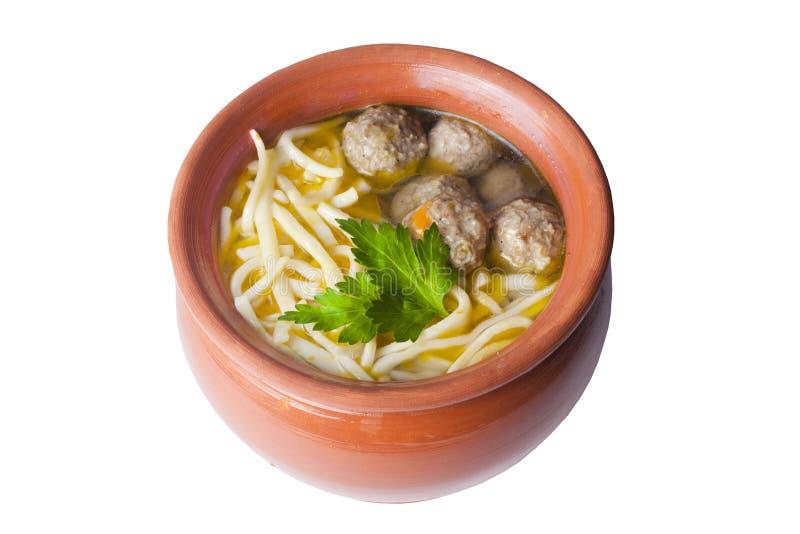 Sopa com massa e almôndegas em um potenciômetro de argila foto de stock