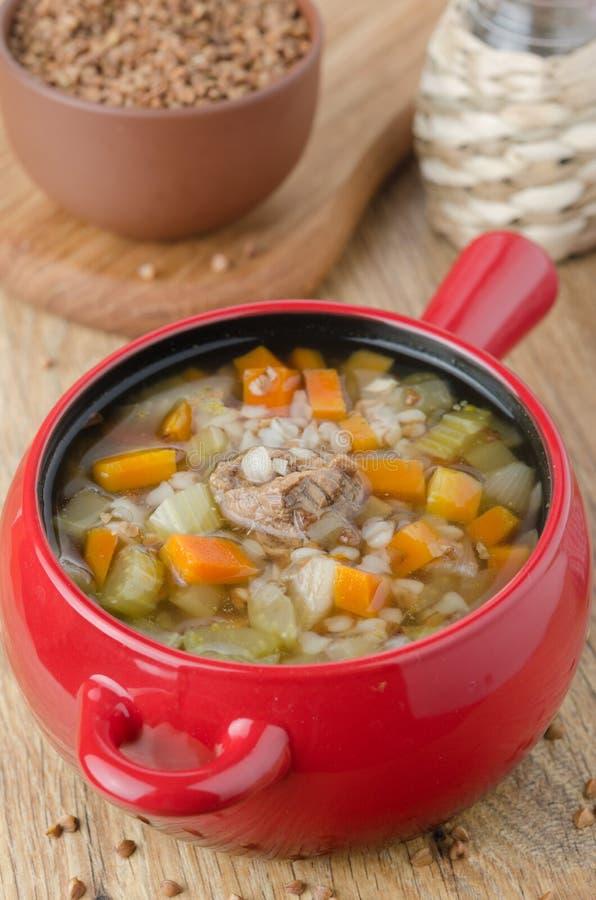 Sopa con carne de vaca y alforfón en un crisol rojo imagen de archivo