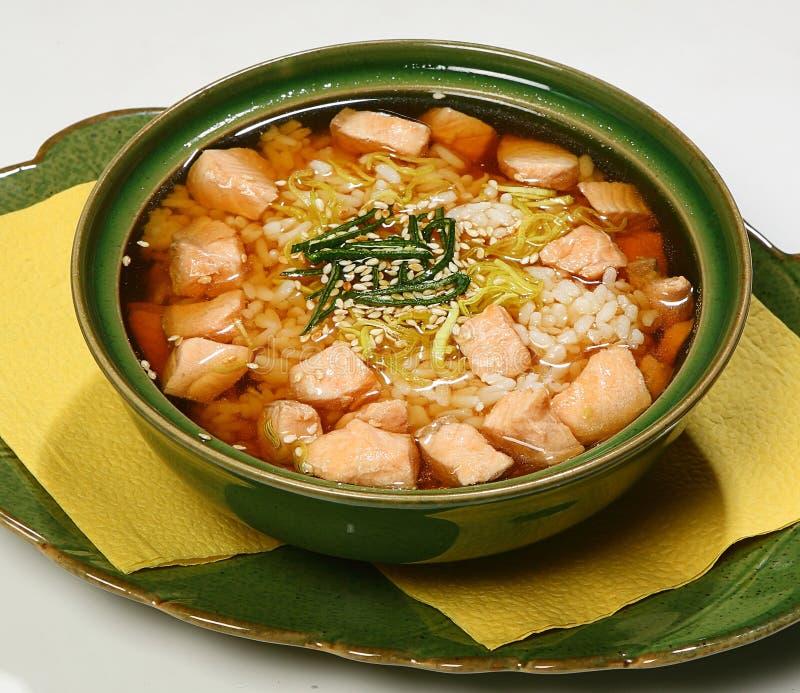 Sopa con el caldo de color salmón del suimono con los salmones, el arroz, el puerro y el sésamo levemente fritos foto de archivo