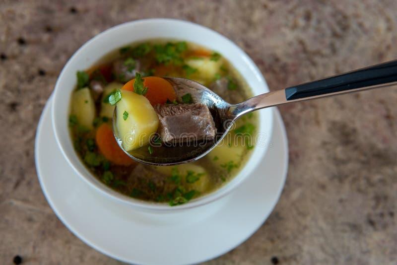Sopa con la carne, las patatas y la zanahoria Sopa de la carne de vaca en un cuenco blanco imagenes de archivo