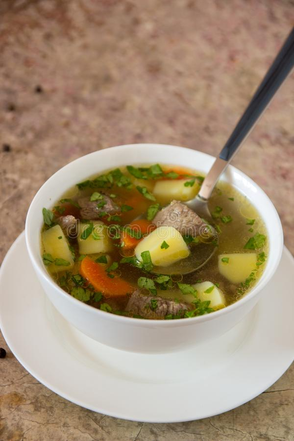 Sopa con la carne, las patatas y la zanahoria Sopa de la carne de vaca en un cuenco blanco, foto de archivo